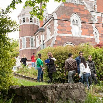 Old red brick building with students standing and talking outside