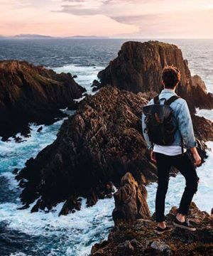 Man standing on rocks looking at the ocean