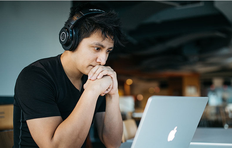 Malaysian student looking at a computer with headphones on