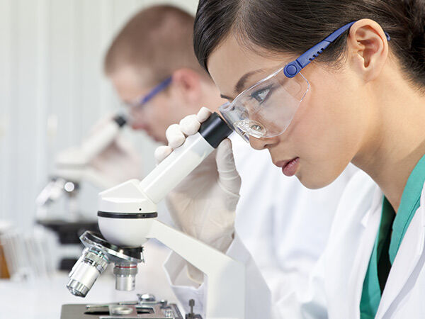 Female student wearing a lab coat and safety googles looking through a microscope