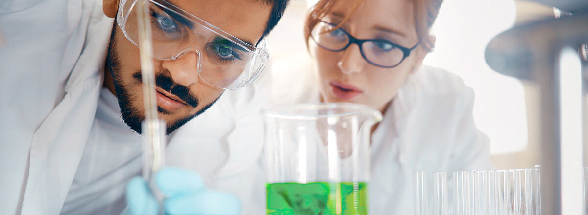 Two people in a lab wearing lab coats and safety googles